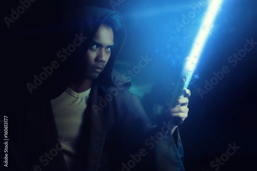 Valokuva Young warrior holding a lightsaber on a dark background