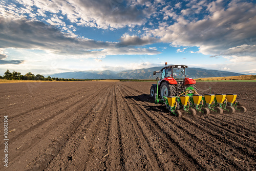 Vászonkép  Agriculture tractor sowing seeds and cultivating field.