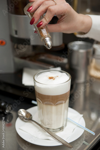 Fototapety, obrazy: Barista decorating latte drink with cocoa powder