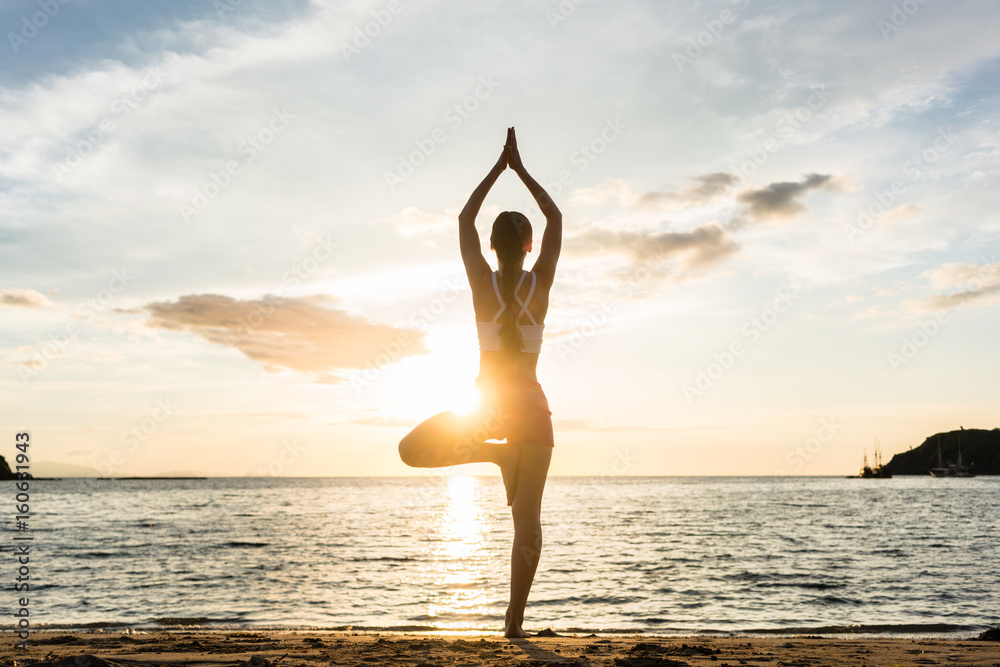 Fototapeta Full length rear view of the silhouette of a woman standing on one leg while practicing the tree yoga pose on a tranquil beach, shot at sunset during summer vacation in Indonesia