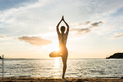 Staande foto School de yoga Full length rear view of the silhouette of a woman standing on one leg while practicing the tree yoga pose on a tranquil beach, shot at sunset during summer vacation in Indonesia