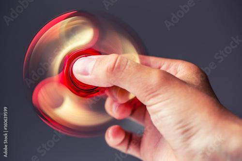 Fototapeta  Fidget Spinner.Red sfidget pinner in a girl hand.