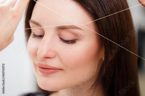 Fotografering  Cosmetologist plucks client eyebrows by thread
