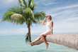 view of nice young lady sitting on palm trunk on tropical beach