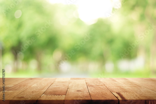 Fotografie, Obraz  Wood table top on blur green background of trees in the park