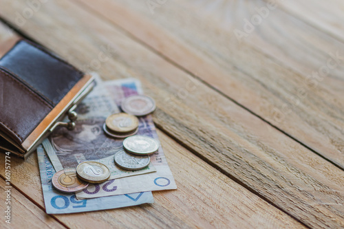 Fotografía  Polish zloty with a little wallet on the old wooden background