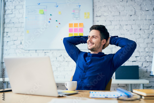 Poster de jardin Detente Satisfied young man in office looking away