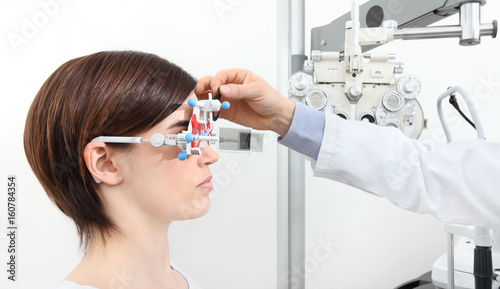 Fotografia optician with trial frame, optometrist doctor examines eyesight of woman patient