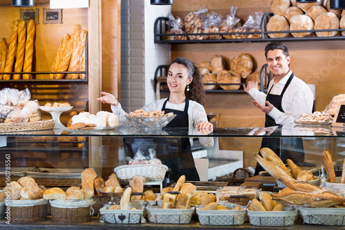 Foto op Canvas Bakkerij Portrait of friendly couple at bakery display with pastry