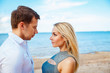 Romantic young couple standing head to head at beach