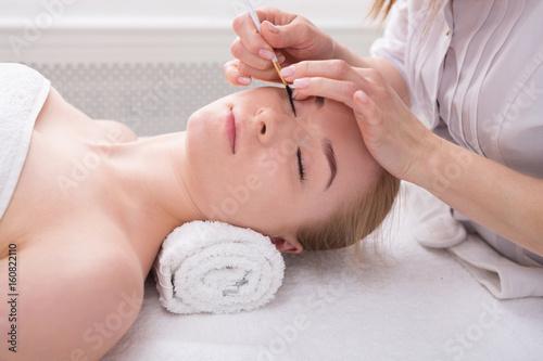 Fototapeta Woman gets eyelashes tinting by beautician at spa