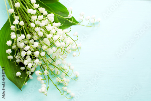 Muguet de mai Bouquet of fresh white lilies of the valley in a wooden window still. Top view