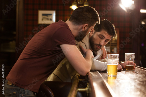 Fototapeta Young man talking to his drunk friend