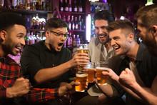 Happy Male Friends Clinking Wi...