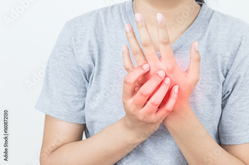 Young woman massaging her painful hand, suffering from hand pain isolated on a w Canvas Print