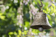 Small metallic oriental bell in the garden, sunny day, greenery