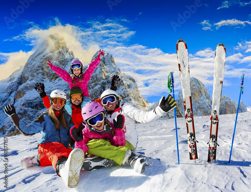 Fotobehang Wintersporten Skiing family enjoying winter vacation on snow in sunny cold day in mountains and fun. San Martino di Castrozza, Italy.