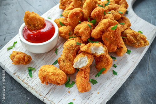 Foto op Canvas Kip Fried crispy chicken nuggets with ketchup on white board