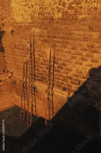 Staande foto Vintage Poster Wooden ladders resting on the walls of the castle