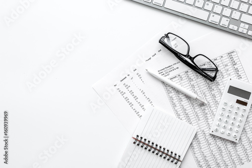 Photo Business report preparing with calculator and glasses on white office background