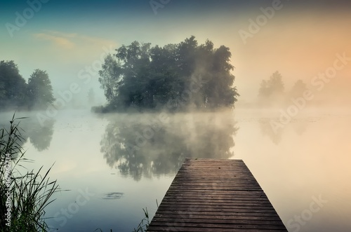 Foto op Canvas Grijs Morning misty landscape on the lake. Wooden pier and island with trees on the lake.
