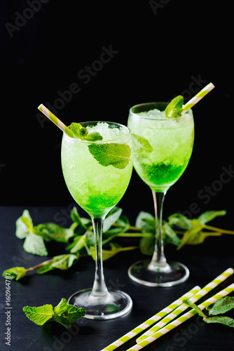 Foto op Plexiglas Bar Green alcoholic or non-alcoholic refreshing summer cocktail, mojito, sparkling drink with mint and ice in a beautiful glass on a dark wooden background