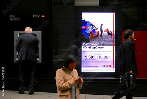 A customer of Europe's biggest bank HSBC uses an ATM next to