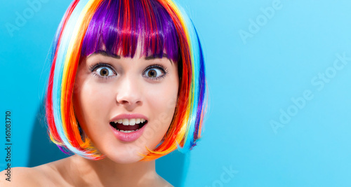 Spoed Foto op Canvas Kapsalon Beautiful woman in a colorful wig on a blue background