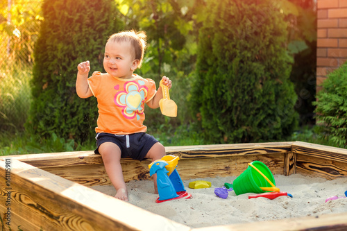 Happy little girl playing in a sandbox on the playground Canvas Print