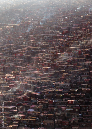 Poster Brick wall Top view monastery at Larung gar (Buddhist Academy) in a warm and foggy morning time, Sichuan, China