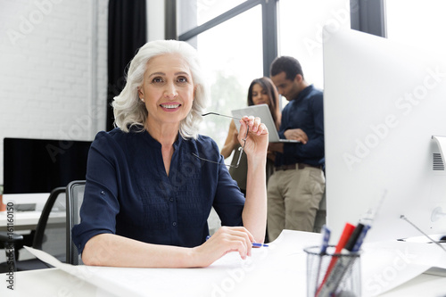 Fotografia Smiling mature business woamn sitting at her workplace