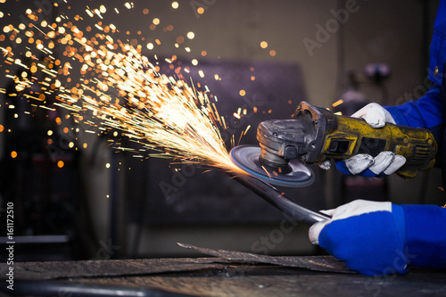 Photo  Grinding a piece of metal pipe and producing sparks.