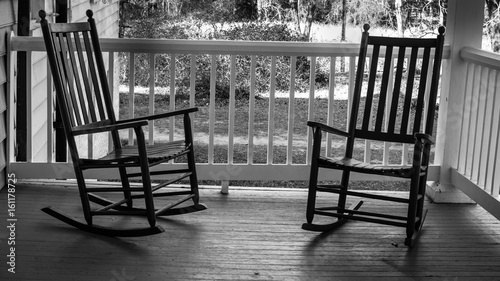 Two Empty Rocking Chairs. Two wooden rocking chairs on a front porch on a warm & Two Empty Rocking Chairs. Two wooden rocking chairs on a front porch ...