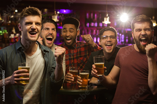 Photo Four happy men holding beer mugs and gesturing