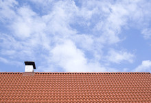 A New Roof With Chimney And Red Tiles Of Cloudy Sky