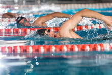 Three Male Swimmers Doing Free Style In Different Swimming Lanes
