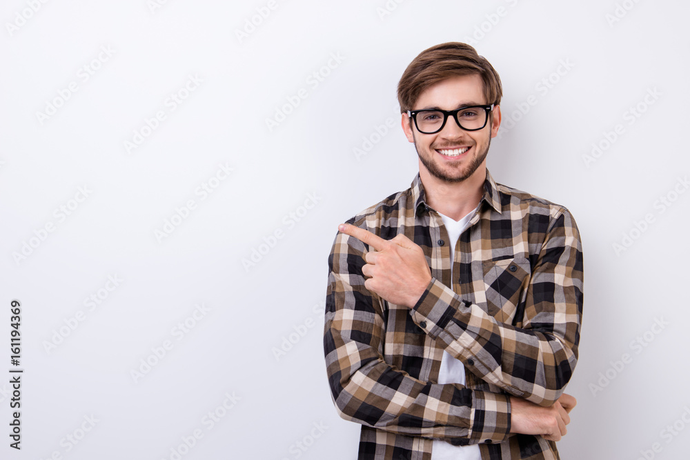 Fototapeta Smiling young nerdy bearded stylish student is standing on pure background in glasses and casual  outfit, pointing on the copyspace