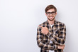 Leinwandbild Motiv Smiling young nerdy bearded stylish student is standing on pure background in glasses and casual  outfit, pointing on the copyspace