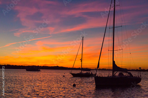 Foto op Plexiglas Crimson Epic and beautiful sunset over harbor with sailboat silouettes