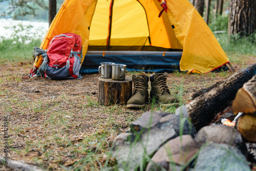 Two metal mugs and shoes in the woods near the fire. Wallpaper Mural