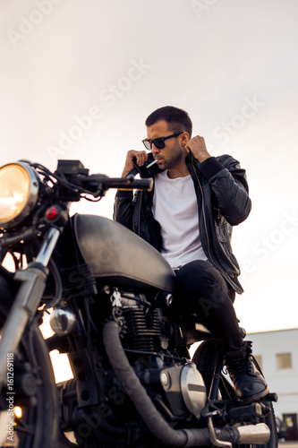 Handsome young rider guy with beard and mustache in black fashion sunglasses smoking cigaret and correct biker jacket sit on classic style cafe racer motorbike at sunset Poster Mural XXL