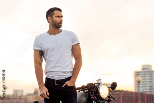 Photo  Sporty biker handsome rider male in white blank t-shirt walk away from classic style cafe racer motorbike at sunset