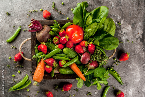 Staande foto Groenten Market. Healthy vegan food. Fresh vegetables, berries, greens and fruits in wooden tray: spinach mint thyme strawberry carrots beets cucumbers radish green peas. On gray table. Copy space top view