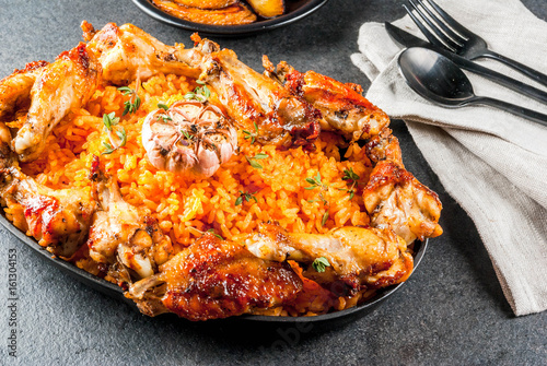 West African national cuisine. Jollof rice with grilled chicken wings and fried bananas plantains.On gray stone table. Copy space