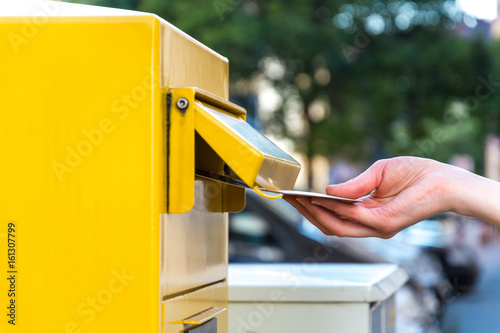 Fotografie, Obraz  Throwing a letter in a yellow mailbox