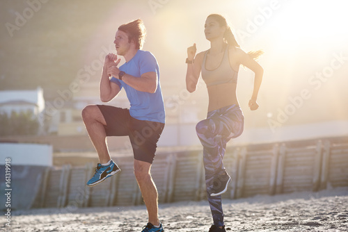 Couple Exercising On Beach