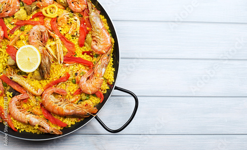 Canvastavla From above paella dish in a pot containing rice and vegetables with seafood