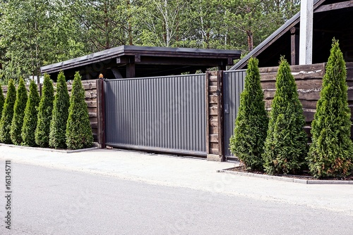 серо коричневые ворота и забор с декоративными зелёными деревьями перед асфальтированной дорогой
