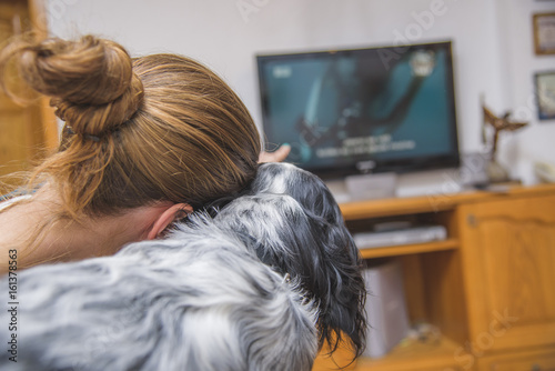 Casual woman and her dog, english setter, watching a movie or