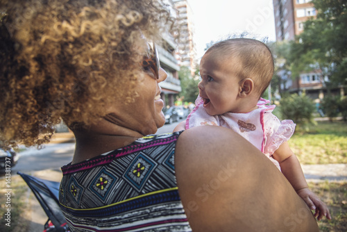 Foto  African american mother kissing her adorable mixed race baby daughter